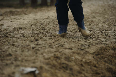 Man with rubber boots walking in the mud