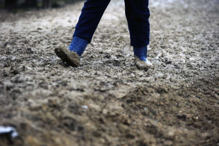 path pathway: Man with rubber boots walking in the mud
