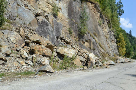 detach: Rockfall in Carpathians where the road is covered with stones