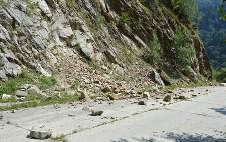 rolling landscape: Rockfall in Carpathians where the road is covered with stones