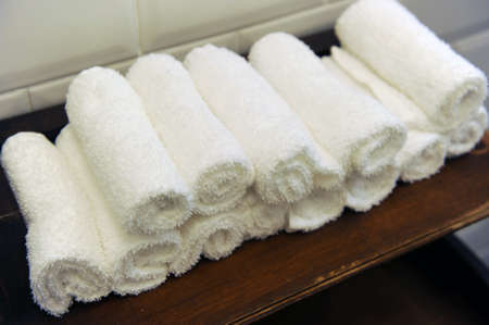 Rolled white towels in a restaurant bathroom