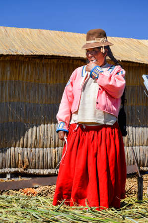 quechua indian: UROS FLOATING ISLANDS, PUNO, PERU. MAY 31, 2013: Unidentified native woman wearing traditional cloths eats sugarcane