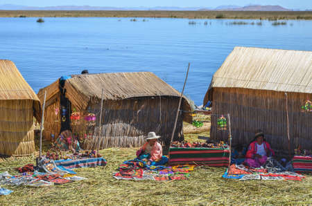 quechua indian: UROS FLOATING ISLANDS, PUNO, PERU. MAY 31, 2013: Traditionally dressed Aymara Uros people live on these islands built on no more than 40 cm thick platforms of reeds in the middle of Titicaca Lake