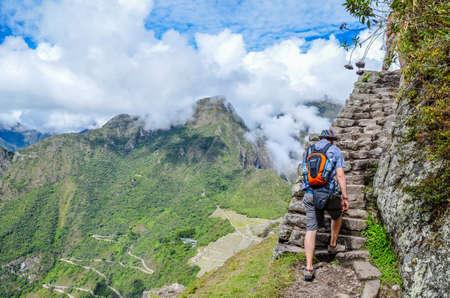 cusco region: MACHU PICCHU, CUSCO REGION, PERU- JUNE 4, 2013: Tourist climbing Huayna Picchu mountain for one of the best panoramic views of Machu Picchu