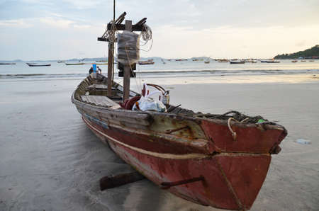 ship wreck: NGAPALI, MYANMAR- SEPTEMBER 27, 2016: Fishermans boat fallen into ruin and disrepair on a beach