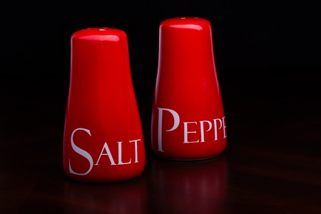 pepperbox: Closup of red gloss, ceramic salt-cellar and pepper-box standing on dark wood table on a black background