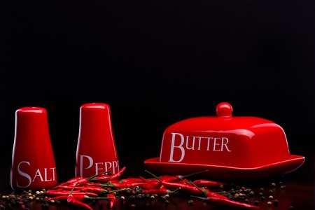pepperbox: Closup of red gloss, ceramic salt-cellar, pepper-box and butter dish with chili and black pepper standing on dark wood table on a black background