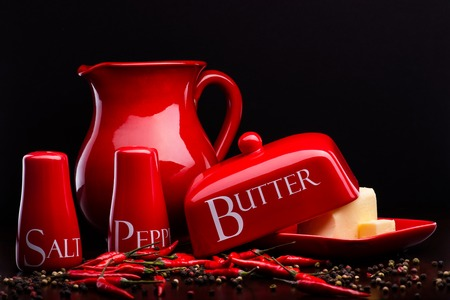 pepperbox: Closup of red gloss, ceramic salt-cellar, pepper-box, butter dish and pitcher with chili and black pepper standing on dark wood table on a black background Stock Photo