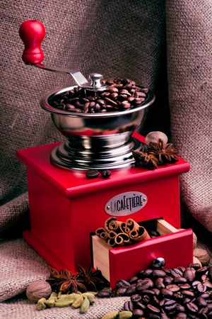 coffeebeans: Coffee grinder on a sackcloth background with coffee beans, anise stars, muscat nut and cinnamon sticks