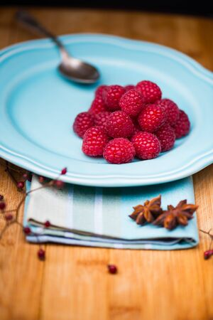 wildberry: Bunch of raspberries on a ceramic blue plate on wood background.