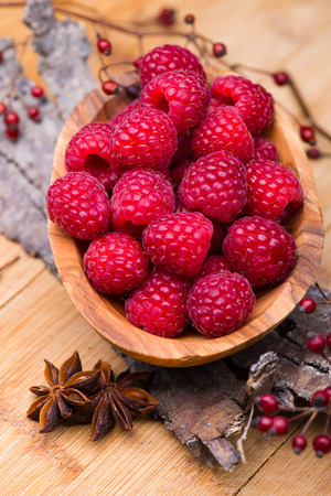 wildberry: Bunch of raspberries in wood bowl on wood and bark background.