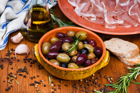 Olives in bow with prosciutto on wooden table and metal vintage spoon Фото со стока