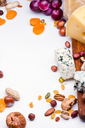Cheeses with dried fruits and nuts on wooden board