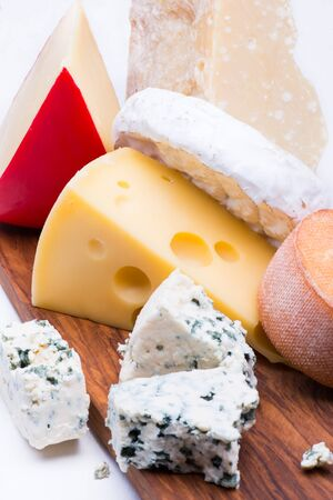 chopping board: Cheeses on chopping board on white background Stock Photo