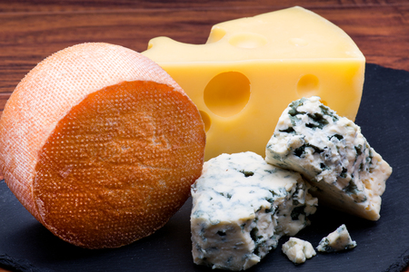 cheese board: Cheeses on cheese board on wooden backgroand Stock Photo