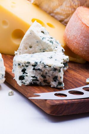 Cheeses on chopping board on white background Imagens
