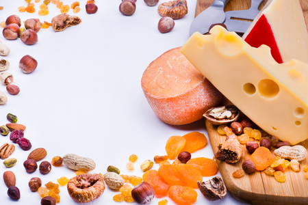 dried fruits: Cheeses with dried fruits and nuts on wooden board