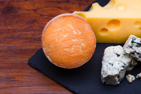cheese board: Cheeses on cheese board on wooden background Stock Photo