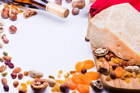 frutas deshidratadas: Queso con frutas secas y nueces sobre tabla de madera