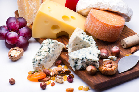 product range: Cheeses with dried fruits and nuts on wooden board