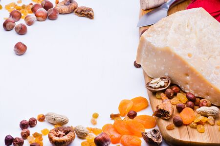 dried fruits: Cheese with dried fruits and nuts on wooden board