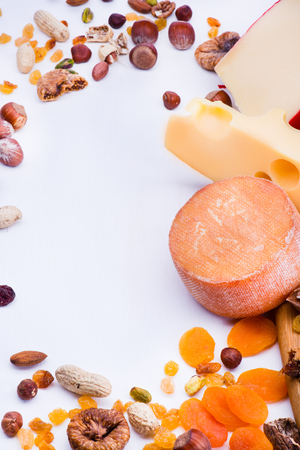 Cheesse with dried fruits and nuts on wooden board