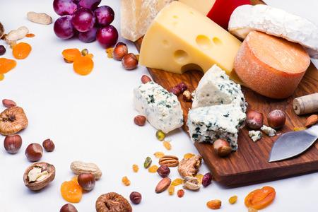 frutos secos: Quesos con frutas secas y nueces sobre tabla de madera