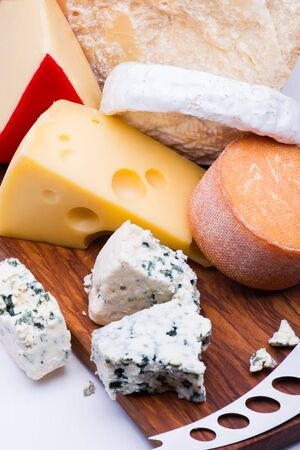 Cheeses on chopping board on white background Stock fotó