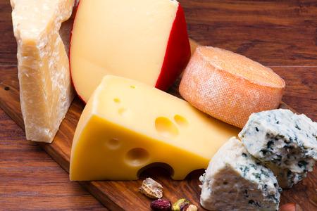 tabla de queso: Quesos a bordo de queso sobre fondo de madera