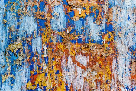 Minimalist colourful textured background of old and rusted whit, blue, brown and orange  paing on metallic surface, in direct sun light in an urban environment Stock fotó