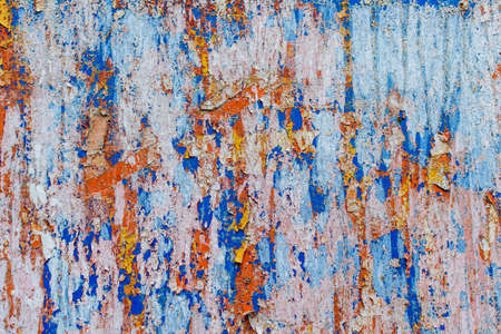 Minimalist colourful textured background of old and rusted whit, blue, brown and orange paing on metallic surface, in direct sun light in an urban environment