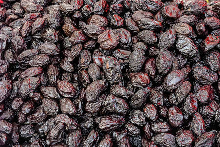Heap of dried dark blue black organic plums displayed for sale at a street food market, top view or flat lay of tasty healthy food photographed with soft focus