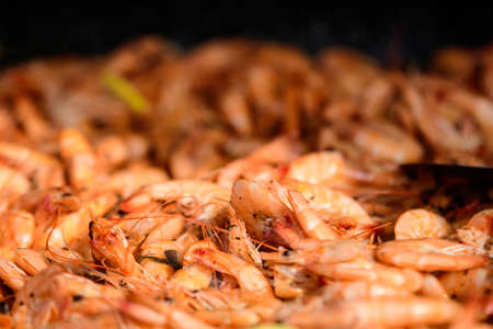 Close up of cooked shrimps with tomato sauce in a large pan at a street food festival, ready to eat seafood