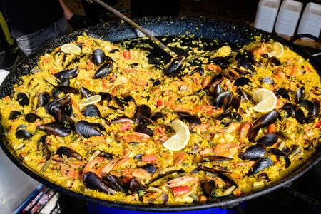 Close up of large portion of traditional Spanish paella dish freshly being cooked with seafood and rice in a frying pan at a street food festival, ready to eat seafood, side view, selective focus
