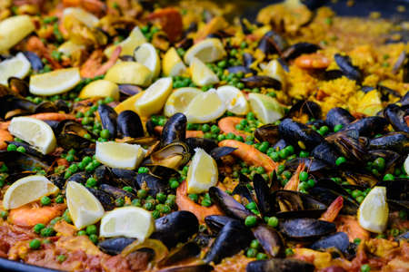 Freshly cooked Spanish paella ready to be served at a street food market, traditional food with rice, shells, shrimps, peas and fresh cut lemons, ready to eat