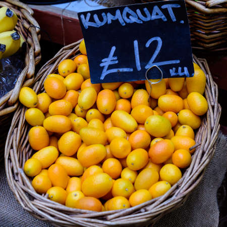 Fresh ripe orange kumkuat fruits displayed with black label and price in a wooden box, at a street food market, ready to eat exotic citrus fruits photographed with soft focus 免版税图像