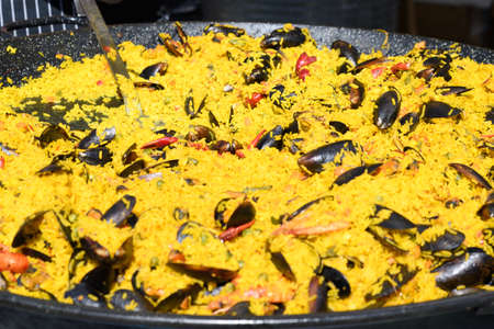 Traditional Spanish paella dish freshly cooked in a large traditional black frying pan at a street food festival, ready to eat seafood, side view
