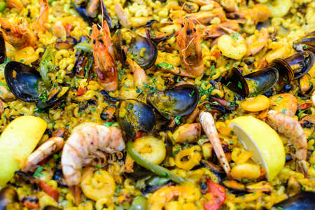 Close up of large portion of traditional Spanish paella dish freshly being cooked with seafood and pasta in a  frying pan at a street food festival, ready to eat seafood, side view, selective focus 免版税图像