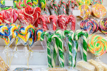 Group of vivid coloured sugar lollipops in display for sale at a candy store in individual plastic packaging, selective focus