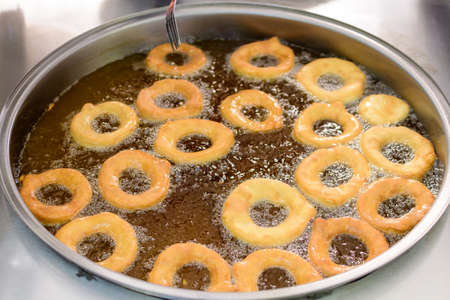Small donuts being deep fried in boiling oil in a large pan, at a street food market, selective focus 免版税图像