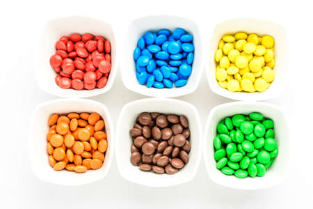 Six white squared bowls with small red, yellow, green, blue, brown and orange coated chocolate candies isolated on white background, top view 免版税图像