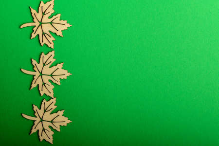 Three delicate light brown wooden leaves on textured green cardboard background, top view with space for text, flat lay with laser cut wooden objects