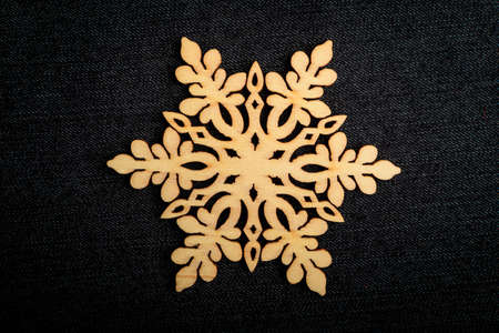One delicate light brown wooden snowflake on black textile material background, displayed on centre, top view with space for text around, flat lay with laser cut wooden object