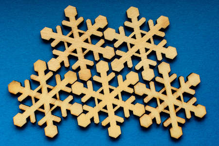 Five delicate light brown wooden snowflakes on blue textures cardboard background, displayed on centre, top view with space for text around, flat lay with laser cut wooden objects 스톡 콘텐츠