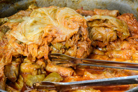 Freshly cooked large portion of cabbage rolls with meat and cabbage, a traditional Romanian food called sarmale cooked at a food market 스톡 콘텐츠