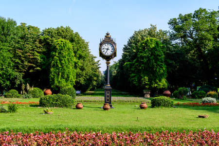 Main entrance with vivid red flowers, green trees and grass in a sunny summer day in Cismigiu Garden in Bucharest, Romania Foto de archivo