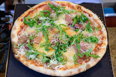 Traditional Italian pizza with prosciutto and rucola (arugula or salad rocket) displayed for sale at a street food market festival in Bucharest, Romania