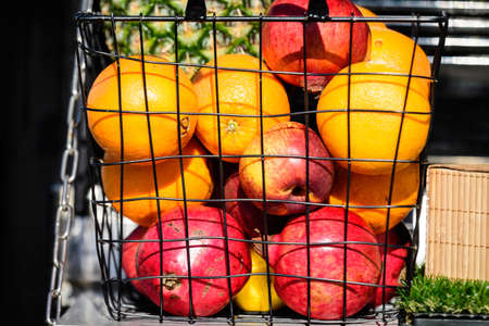 Orange, red apples and pomegranate fruits in a metallic basket displayed for sale at a street food market in Bucharest, Romania, side view of healthy fruits photograph with soft focus