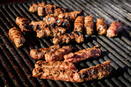 Grilled meat rolls called Mici or Mititei, traditional fresh Romanian bbq grill food cooked on the barbeque at a street food market Foto de archivo