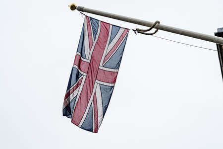Flag of United Kingdom (the Union Jack also known as Union flag) blowing in the wind towards cloudy grey sky in a rainy day Stock Photo